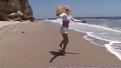 Busty blonde in beach fingering