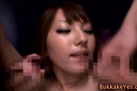 Hot asian babe sucking on two cocks and getting face jizzed