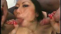 Horny asian whore showing her tits and ass before sucking on two cocks