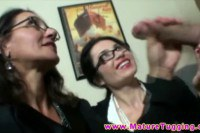 Two busty brunette MILFs with spex jerking off a guy
