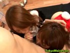 Two kinky japanese babes sucking on a dude's cock