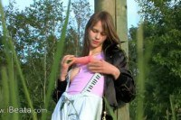 Innocent beauty toying her asshole in nature