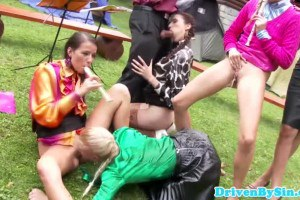 A bunch of glam fetish singers sucking a huge cock outdoors