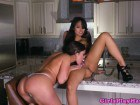 Two curvy brunettes rubbing each other's twats in the kitchen