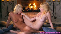 Two classy blondes scissoring pussies by the fireplace