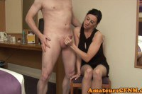 Classy British brunette in dress gives handjob to naked guy
