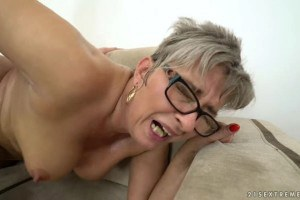 Jessye short haired mature with glasses enjoys a young cock on the sofa