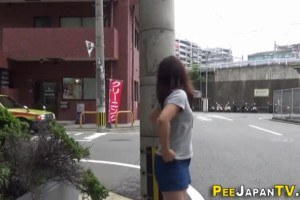 Asian pees a stream on the street