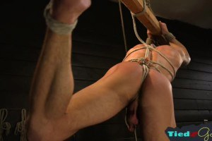 Muscly hunk whipping his tiedup submissive