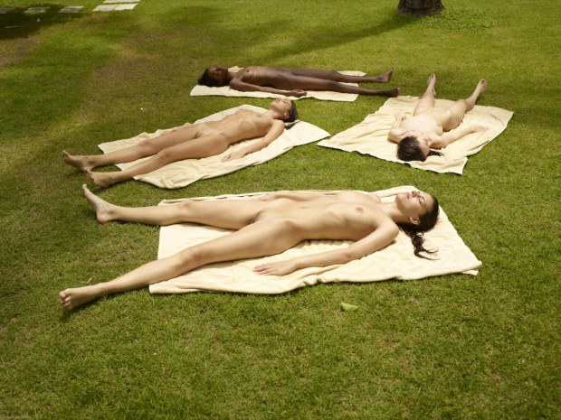 A bunch of nudists catching sun in the park