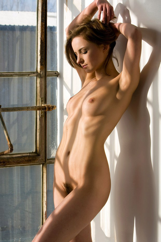 Naked babe model teases by the window