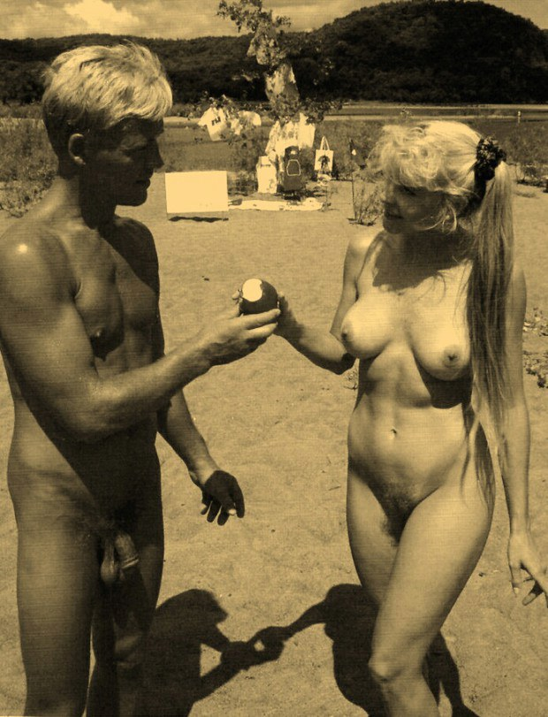 Vintage nudists sharing an apple at the beach