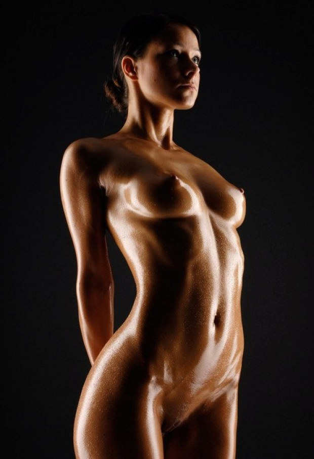 Brunette oiled up model presents her perky tits