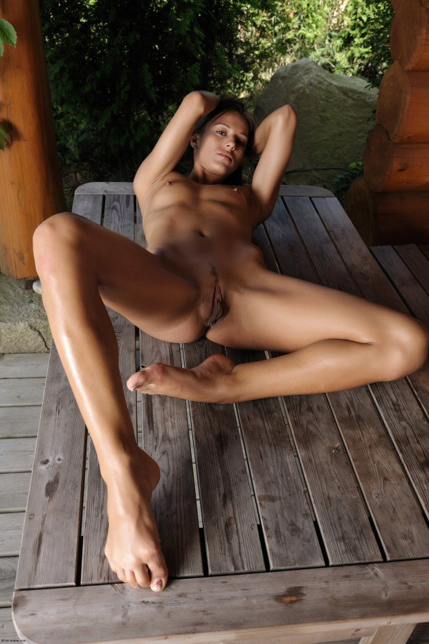 Tanned babe with small tits is naked outdoors
