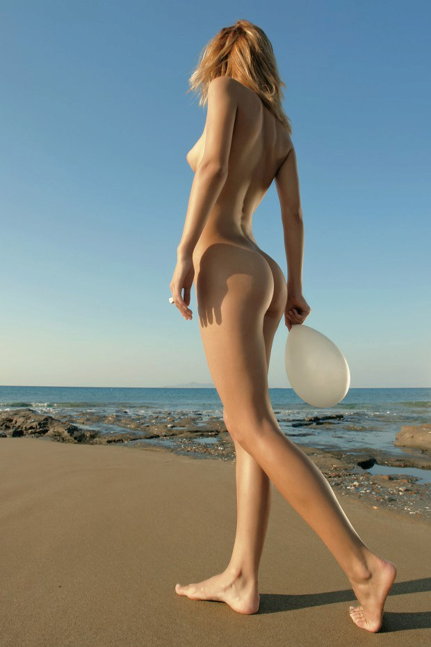 Slender blonde model walks naked on the beach