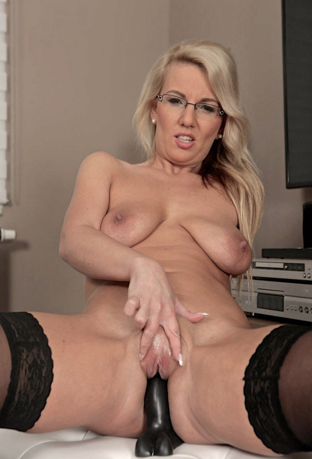 Blonde cougar with glasses rides her black dildo