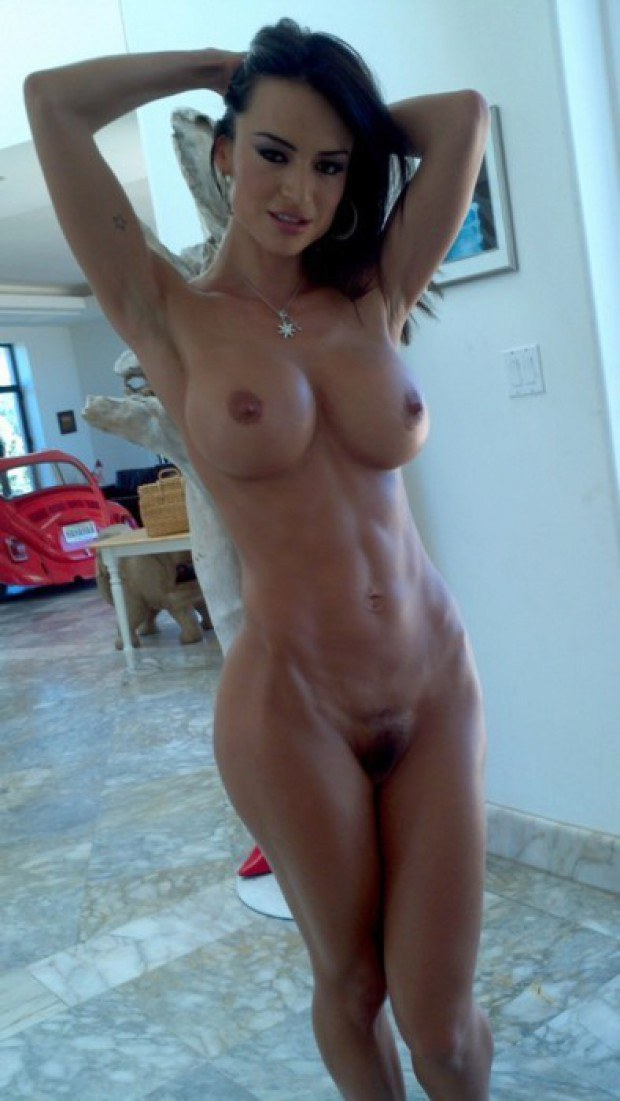 Muscular brunette doll teases with her big boobs