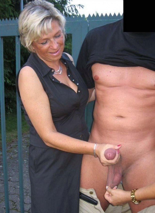 Mature wife wanks a guy's boner outdoors
