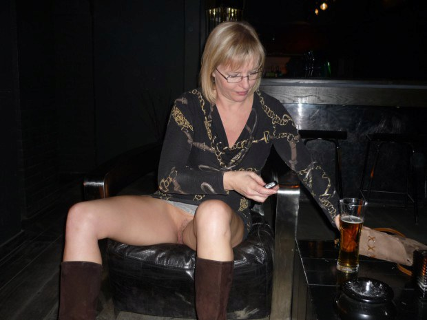 Blonde wife exposes her shaved pussy at the bar