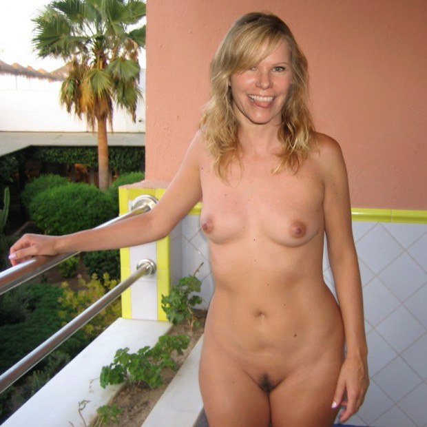 Blonde wife is naked in the balcony on vacation