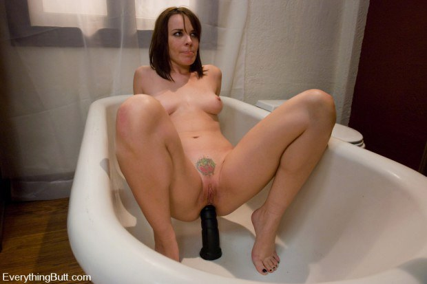 MILF rides a black dildo in the bathtub